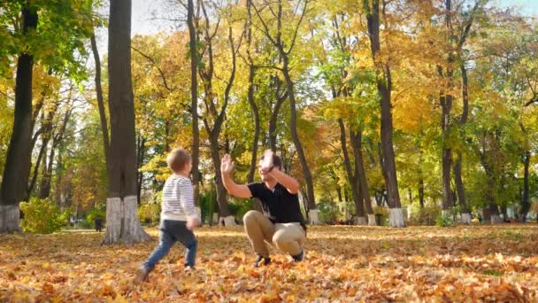 4k video of cheerful smiling little boy running to his, giving him five and hugging in autumn park
