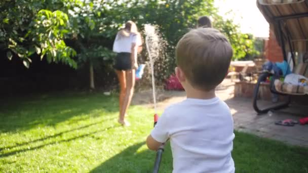 4k slow motion video of little toddler boy playing with two girls with water garden house at backyard