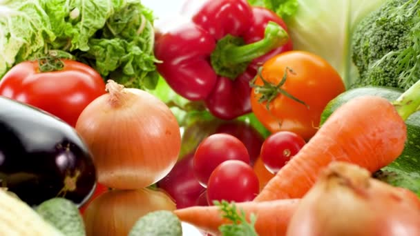 4k dolly video of big assortment of fresh seasonal vegetables against white background. Concept of healthy nutrition and organic food. Perfect shot for vegetarian or vegan