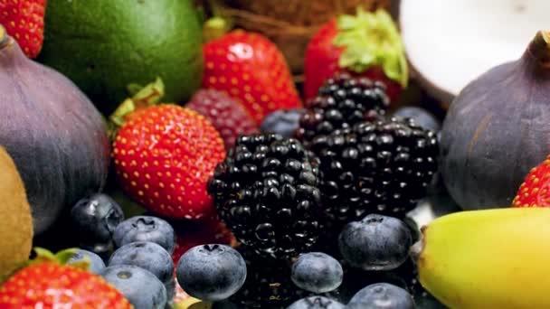 4k Dolly video fotoaparátu pomalu se pohybuje směrem k tropické ovoce. Banány, jahody, avokádo, kokosové ořechy, pomeranče, ananas, fíky, jablka, pomeranče, borůvky hrozny ležící na stole. Dokonalé