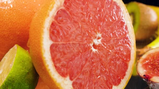 Closeup 4k video of water droplet falling and rolling ooff cut fresh grapefruit. Perfect shot for organic food and healthy nutrition.