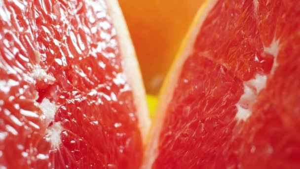 Closeup video of camera moving between two halves of freshly cut orange or grapefruit. Perfect abstract shot for organic food and healthy nutrition. Closeup of citrus fruits