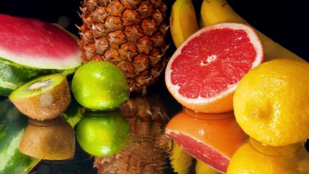 Lassú mozgású videó vízcseppekről, amelyek a trópusi gyümölcsök választékának esnek szembe fekete háttérrel. Tökéletes absztrakt felvétel organikus ételekhez és egészséges táplálkozáshoz. Trópusi gyümölcsök közelsége