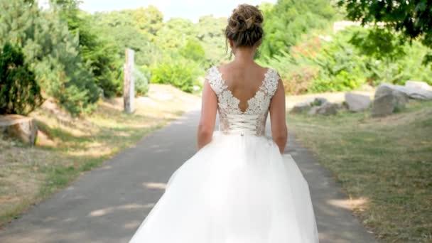 4k lassított felvétel fiatal gyönyörű menyasszony hosszú fehér ruha sétál el az utat a parkban