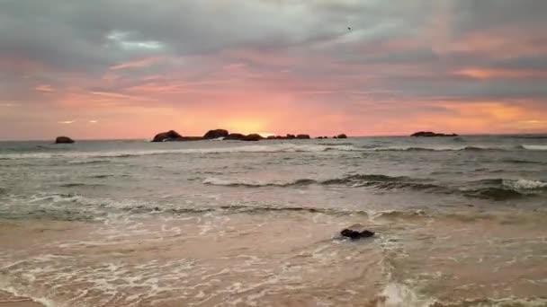 4k videó gyönyörű naplementéről a sziklák felett az óceánban