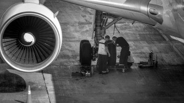 Black and white image of maintenance ground crew checking and repairing airplane chassis wheels before taking off. stock vector