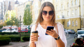 Portrait of beautiful female student with cup of coffee browsing internet on smartphone