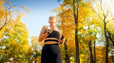 Portrait of beautiful sexy woman exercising and running in autumn park at sunrise