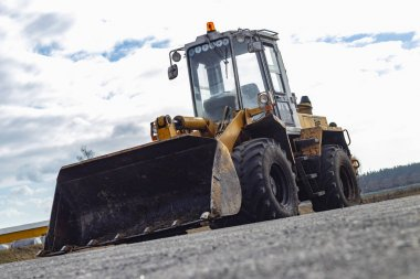 Daylight Yellow loader with a bucket. There is a tint. Close-up.