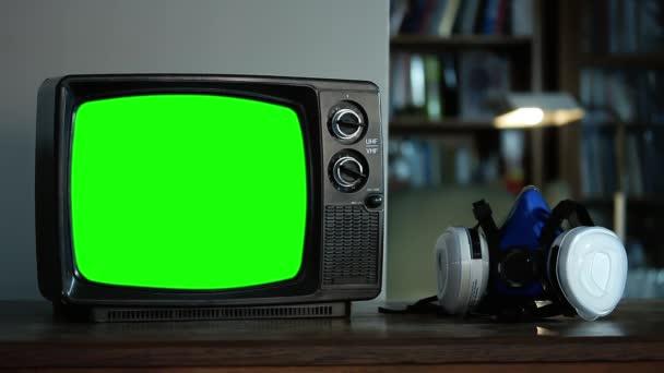 Kézzel felvesz egy arclélegeztető maszkot és egy retro TV-t zöld képernyővel. Közelkép. Kicserélheti a zöld képernyőt a felvételre vagy képre, amit akar. Megteheted a Keying effektussal (nézd meg az útmutatókat a YouTube-on).