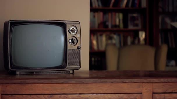 Egy ember elüt egy régi TV-t jel és zaj nélkül a képernyőn, ami zöldre vált. A zöld képernyőt helyettesítheti a kívánt képpel vagy képpel az After Effects billentyűzettel.