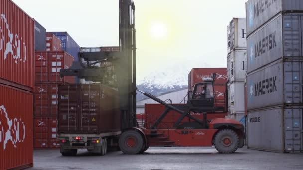 Ushuaia, Feuerland / Argentinien - 09 09 2019: Containerterminal mit Kran beim Entladen eines Containers von einem LKW in Ushuaia, Argentinien.