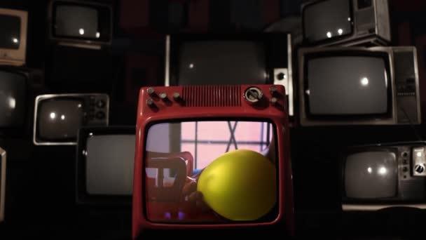 Sárga hélium léggömb felrobban egy retro TV, amely eltörik.