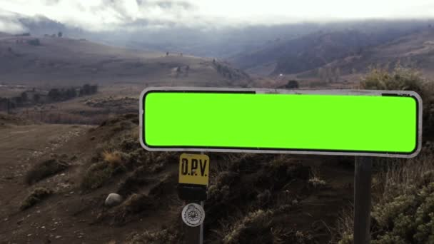 Empty Green Road Sign in a Dirt Road in Patagonia. The Andes Mountains in the Background. Close Up. Zoom In. You can replace green screen with the footage or picture you want. You can do it with Keying (Chroma Key) effect in Adobe After Effects.