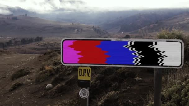 Road Sign with Color Bars in a Dirt Road and a Mountain Background. Close Up. Zoom In.