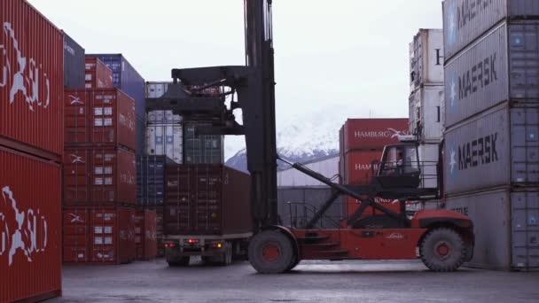 Containerterminal mit Kran beim Entladen eines Containers von einem LKW. Gedreht in Ushuaia, Argentinien.