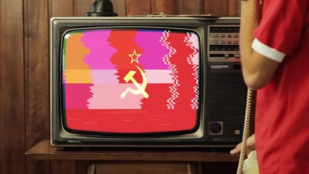 Fiatalember beszél a régi telefon otthon és nézi a Vörös Szovjetunió zászló egy retro TV.