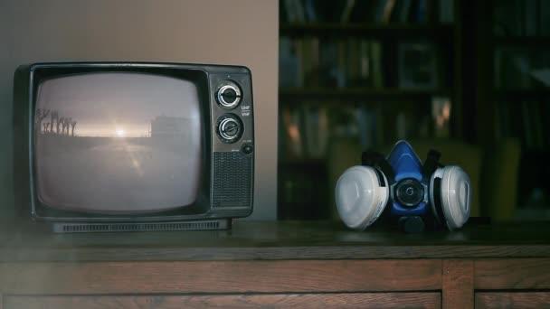 Egy férfi felvette a lélegeztető maszkot és egy retro TV-t egy Elpusztult Világgal a képernyőn. Füst háttér. Coronavirus Pandémiás Járvány Fogantatás Videó. Közelkép.