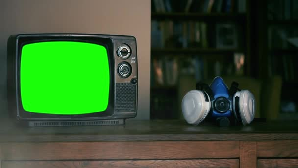 Kézzel felvesz egy arclélegeztető maszkot és egy retro TV-t zöld képernyővel. Füst háttér. A zöld képernyőt helyettesítheti a kívánt képpel vagy képpel az After Effects billentyűzettel.