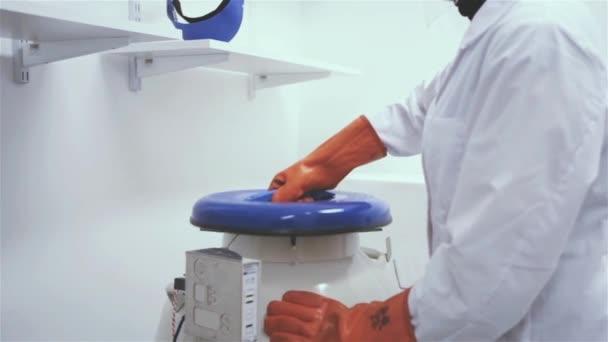 Eine Labormitarbeiterin öffnet einen Flüssigstickstofftank. Nahaufnahme.