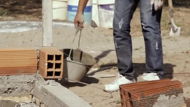 Construction Worker building a Brick Wall with a Spatula and a Cement Bucket in a Poor Neighborhood in South America.
