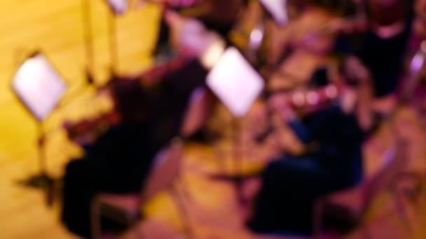 Szimfonikus zenekari zenészek a színpadon befejező játék. Homályos fókusz. Hegedűs