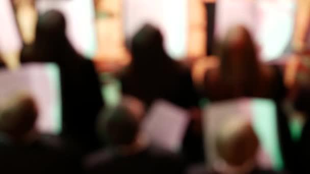 Symfoničtí orchestroví hudebníci na jevišti. Sbor stojí vzadu a tancuje.