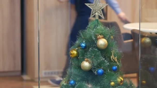 Vánoční stromek s hračkami a zlatou hvězdou nahoře. Vánoční koule zlaté
