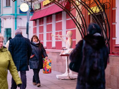 Moscow, Russia - January 17, 2020: Entrance to street cafe in city center in evening. Porch with light illumination and soviet union era sculpture of pioneer with clarion. Sign text Varenichnaya No.1