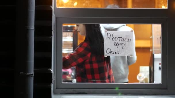 Woman merchandise at street cafe. Text - working through window.