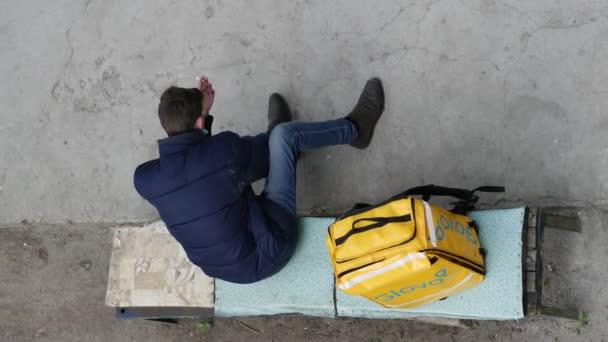 GLOVO Lieferkurier mit gelbem Thermorucksack für Kundenaufträge.