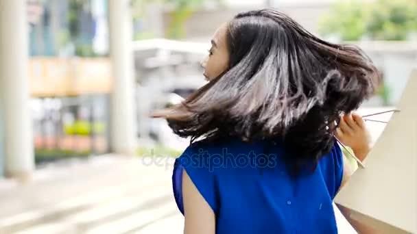 Asijská dívka běží, chodí kolem sebe. Ona je šťastná nakupování