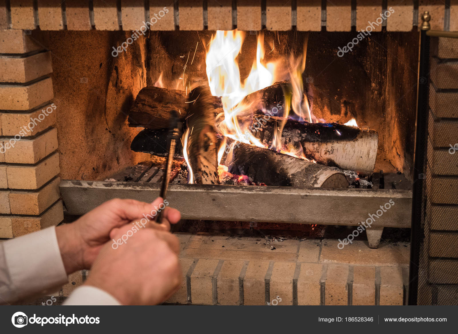 Man Putting Wood Logs Fireplace Stock Photo