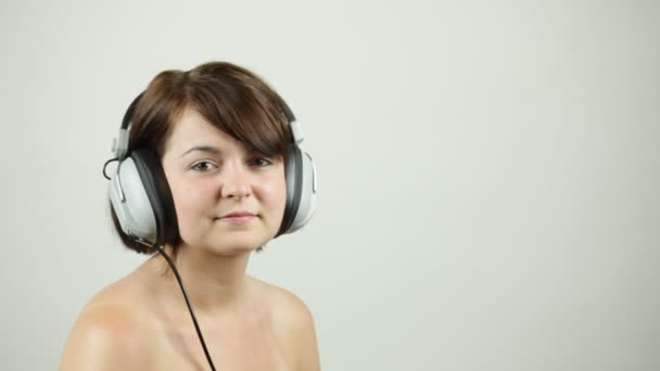 Set of studio shots of a pretty auburn haired woman listening to music with retro headphones and playing to the camera