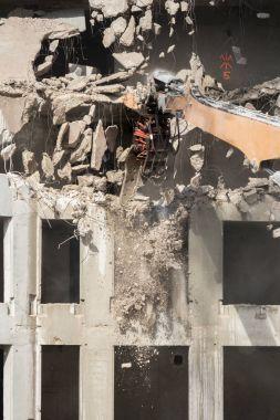 Demolition of concrete building with excavator