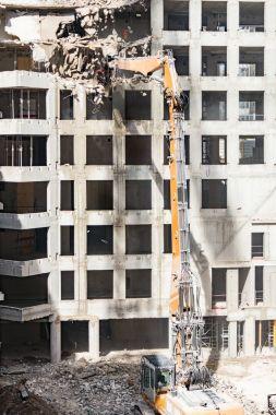 demolition of high concrete building with excavator