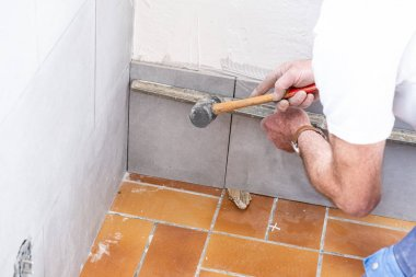 the tiler lays a ceramic tile on the wall