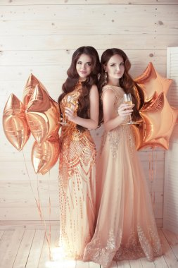 Two Girls on party. Beautiful young women in elegant golden dres