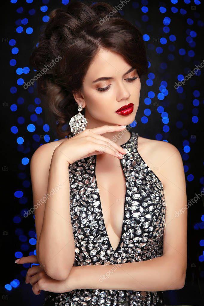 a893e3edf55fdc Sieraden. Kapsel. Mode vrouw. Mooie elegante dame in sexy zwarte jurk en  dure oorbellen. Glamour foto. Slank model geïsoleerde portret op zwarte  achtergrond ...