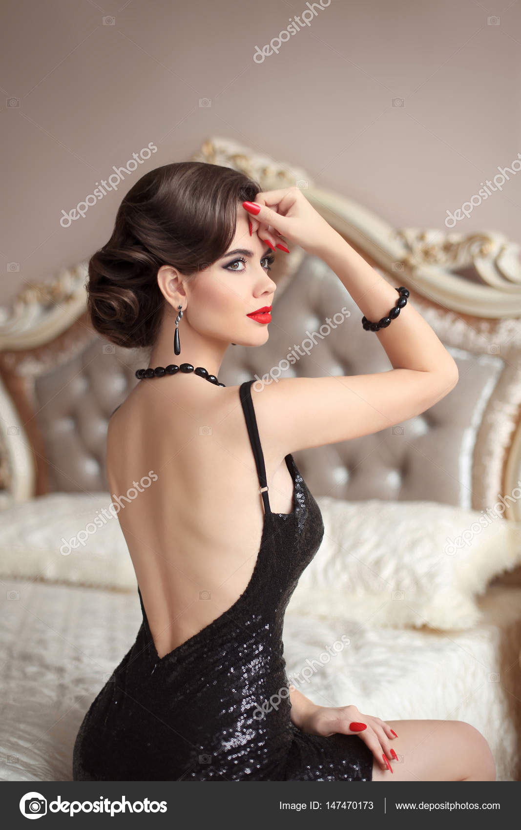 Beautiful back of elegant woman in black sexy dress posing on modern bed in bedroom  interior. Luxury life. Fashionable Brunette girl with gems jewelry set. bd2d51592