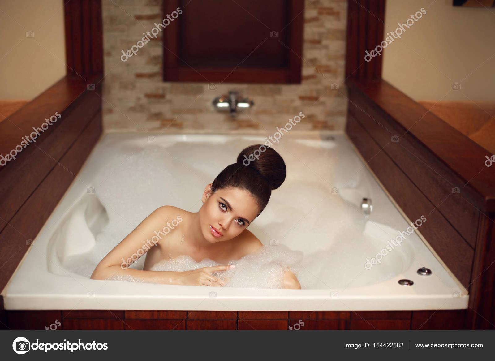 Young woman relaxing in foam jacuzzi bath spa, brunette enjoying ...