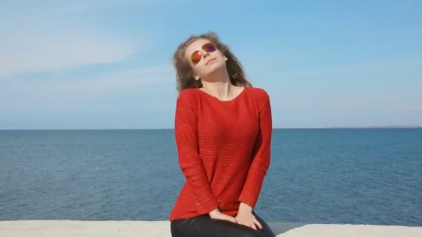 Close up portrait of woman in fashion trendy sunglasses running hand through curly hair blowing in wind by sea on beach. Happy female over blue sky