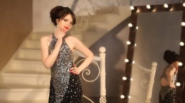 Elegant lady, young model in luxury black dress posing, cute girl in front of the mirror with light bulbs in the dressing room. Brunette with makeup and hairstyle.
