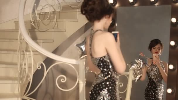 Selfie. junges Glamour-Mädchen beim Fotografieren in elegantem Kleid. modische Dame mit Frisur und Make-up posiert mit Spiegel mit Glühbirnen in Luxus-Wohnung.