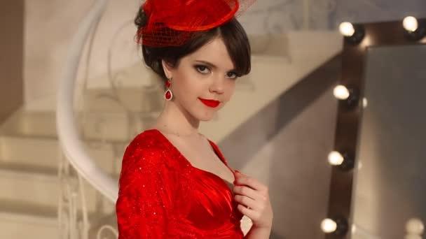 Detailní mladé dívky nádherné módní retro klobouk a červených šatech, Bruneta model s červenými rty make-up, elegantní účes, přívěsek ženy sada šperky představují zrcadlo s žárovkami pro make-up v oblékání