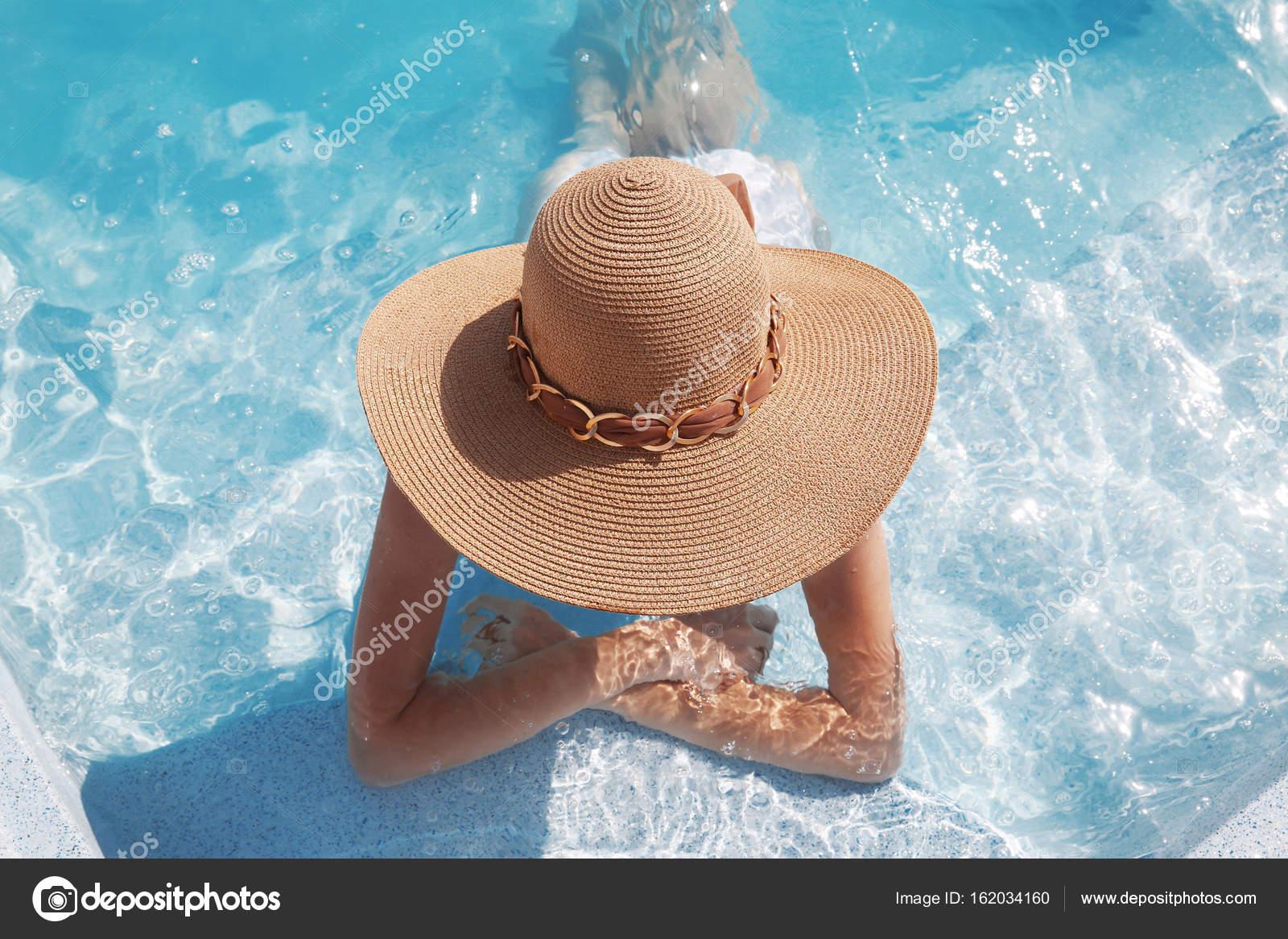 e56ff2d6c7 Mulher na praia desfrutando de chapéu na piscina no luxuoso resort  tropical. Paraíso exótico. Viagens, turismo e conceito de férias — Foto de  VictoriaAndrea