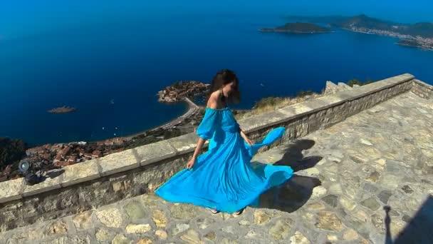 Krásná bruneta usmívající se dívka s zdravé dlouhé vlasy ve větru a šaty. Šťastná mladá žena těší a baví nad mořem a modrá obloha. Sveti Stefan, Černá Hora.