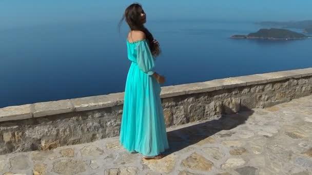 Krásná bruneta usmívající se dívka s zdravé dlouhé vlasy ve větru a šaty. Šťastná mladá žena užívat si přírody a baví nad mořem a modrá obloha. Sveti Stefan, Černá Hora.