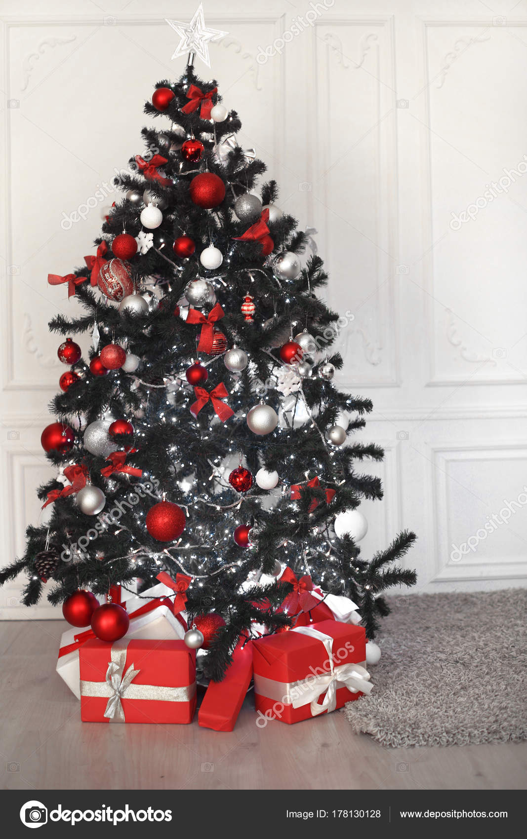 Christmas Tree With Red Gifts Decoration Before White Wall In Ho Stock Photo Image By C Victoriaandrea 178130128