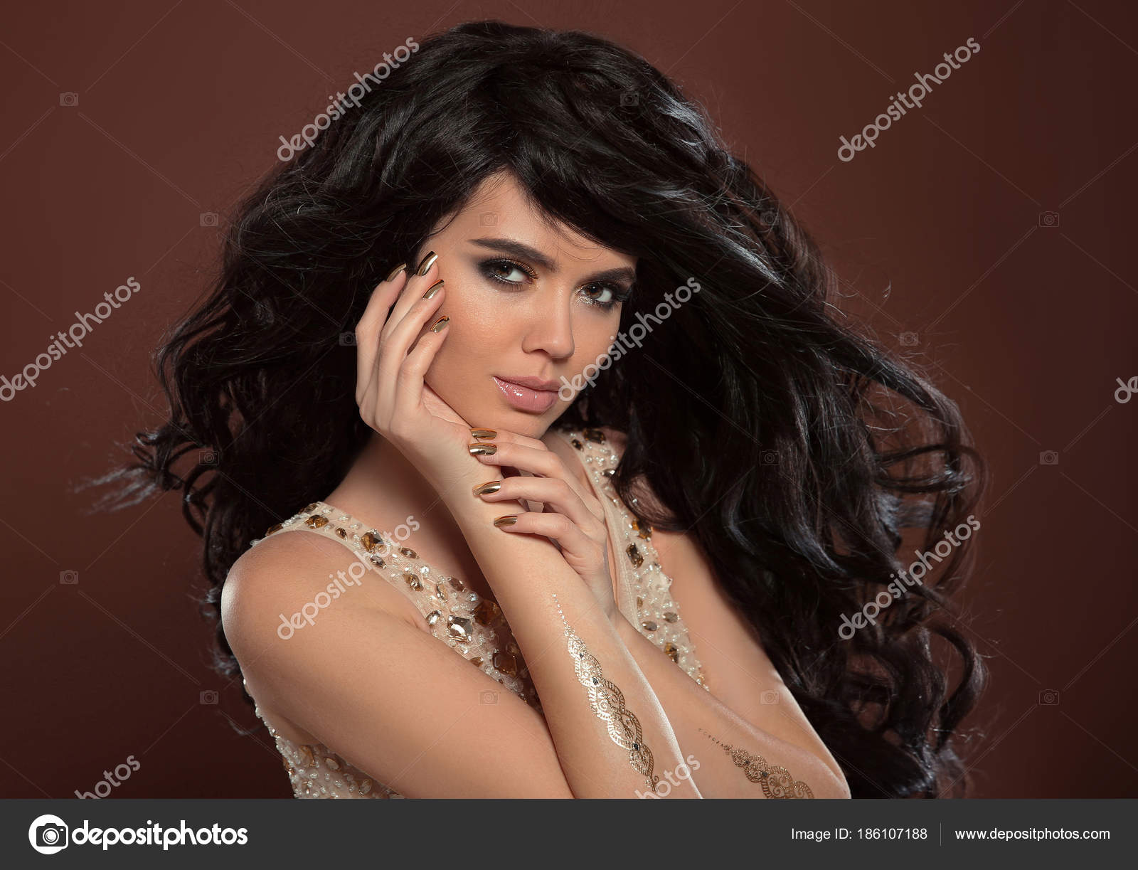 Beauty hair and golden manicure nails. Beautiful brunette model ...